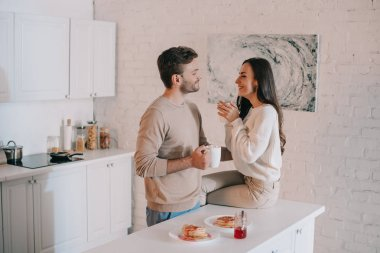 smiling young couple having breakfast together and chatting at home