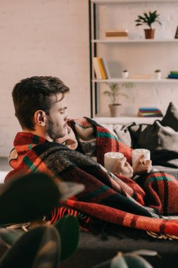 beautiful young couple with cups of cocoa with marshmallow relaxing on couch under plaid at home