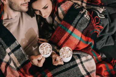 top view of young couple with cups of cocoa with marshmallow relaxing on couch under plaid at home