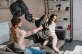 laughing young couple fighting with pillows on couch at home