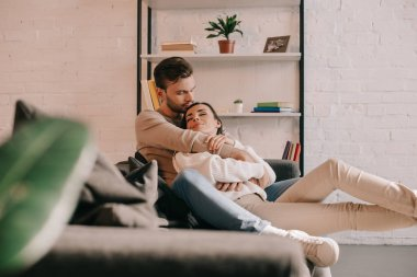 attractive young couple embracing on couch at home