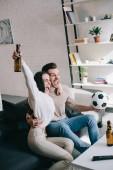 Fényképek boldog kifejező a fiatal pár néz foci játék, otthon és éljenzés
