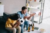 Fényképek kifejező dühös fiatal pár figyel labdarúgó játék otthon