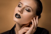 Fotografie young beautiful woman with glittery makeup and hands near face