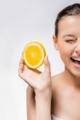 mladá žena s přimhouřeným okem a plátek pomeranče
