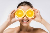 young smiling woman with orange slices on eyes