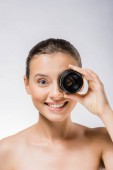Fotografie young smiling woman holding lens near eye