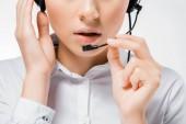 Detailní záběr z mladých call centrum operátor dotýká sluchátka a mluvení do mikrofonu