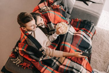 high angle view of beautiful young couple watching tv with popcorn on couch and covering with plaid