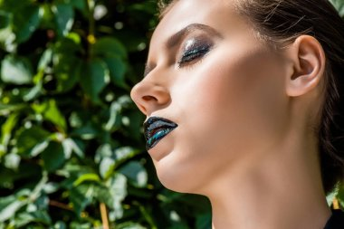 young woman with black lips and green leaves at background