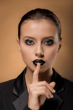young beautiful woman with glittery makeup and finger near lips