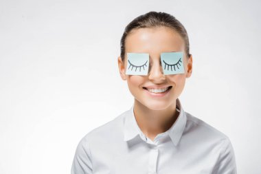 young smiling woman with sticky notes on eyes and drawn eyelashes