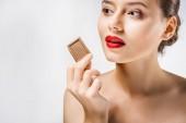 Fotografie junge schöne Frau mit roten Lippen mit Schokolade Stück