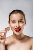 Fotografie junge schöne Frau mit roten Lippen halten Schokolade Stück und leckte die Lippen