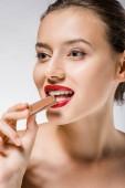 Fotografie junge schöne Frau mit roten Lippen beißt Schokoladenstück
