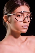portrét krásné ženy v módní brýle s odhalenými rameny při pohledu na fotoaparát izolované na černém pozadí