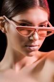 Fotografie portrét krásné modelu v módní brýle při pohledu na fotoaparát izolované na černém