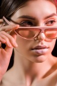 portrét krásné modelu v módní brýle při pohledu od izolovaných na černé