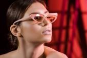 Fotografie portrét stylového modelu v brýlích pózuje na tmavém pozadí
