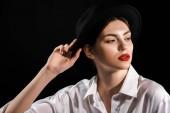 Porträt des modischen Modells in weißem Hemd und schwarzem Hut isoliert auf schwarz