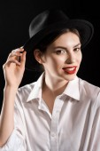 stylish smiling model with red lips in white shirt and black hat posing isolated on black