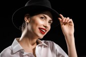 portrait of beautiful smiling woman in white shirt and black hat posing isolated on black