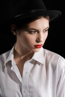Portrait of fashionable model in white shirt and black hat isolated on black stock vector