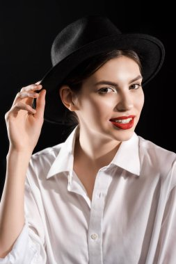 Stylish smiling model with red lips in white shirt and black hat posing isolated on black stock vector