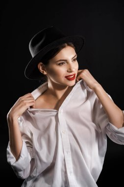 Stylish young model with red lips in white shirt and black hat posing isolated on black stock vector