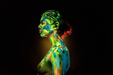 side view of woman painted with colorful ultraviolet paints on black backdrop