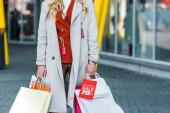 Fotografie Blick auf Frau mit Einkaufstüten und Verkaufsschild beschnitten