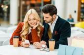 Fényképek mosolygó pár használ smartphone, kávézó, kávé, hogy menjen és a bevásárló szatyrok