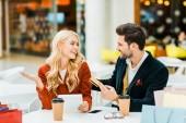 Fényképek boldog elegáns pár vásárolni online hitel kártya és a tabletta, miközben ül a kávézó, bevásárló központ