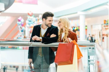 Beautiful young couple with shopping bags spending time in mall stock vector