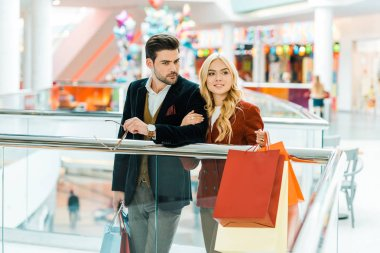 young couple with shopping bags spending time in shopping center