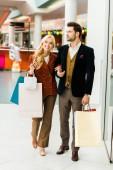 Fotografie mladý, šťastný pár s nákupníma taškama v nákupní centrum