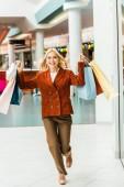 krásná vzrušená žena s nákupní tašky v obchoďáku