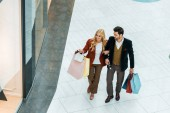 overhead view of young couple with shopping bags walking in shopping mall