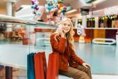 Fotografie Módní mladá žena mluví o smartphone a sedí s taškami v nákupní centrum