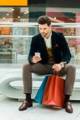 Fotografie pohledný muž pomocí smartphone v nákupní centrum s vaky