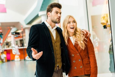 young emotional couple spending time in shopping center