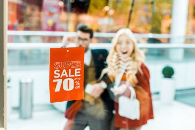 selective focus of super sale with 70 percents discount and couple in shopping mall