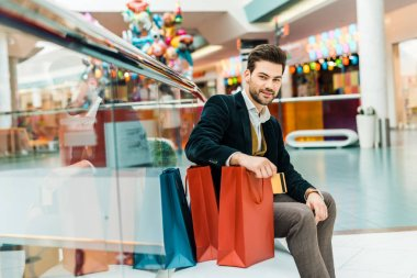 stylish elegant man sitting in shopping mall with bags