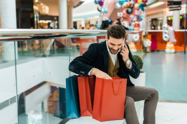 handsome man talking on smartphone and looking into bags while sitting in shopping mall