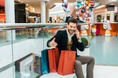 handsome fashionable man with shopping bags talking on smartphone while sitting in shopping mall