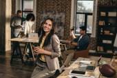 usmívající se neformální podnikatelka drží kávy v kanceláři podkroví s kolegy pracující za