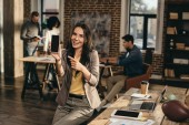 Photo smiling casual businesswoman holding smartphone with blank screen in loft office with colleagues working behind
