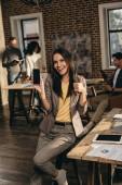 příležitostné podnikatelka držení smartphone s prázdnou obrazovkou a ukazuje palec nahoru znamení v podkroví úřadu s kolegy pracující za