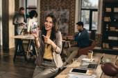 s úsměvem příležitostné podnikatelka držení smartphone s aplikací pinterest v podkroví úřadu s kolegy pracující za