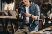 Photo cropped view of smiling young man pointing finger on smartphone in modern loft office with colleagues on background